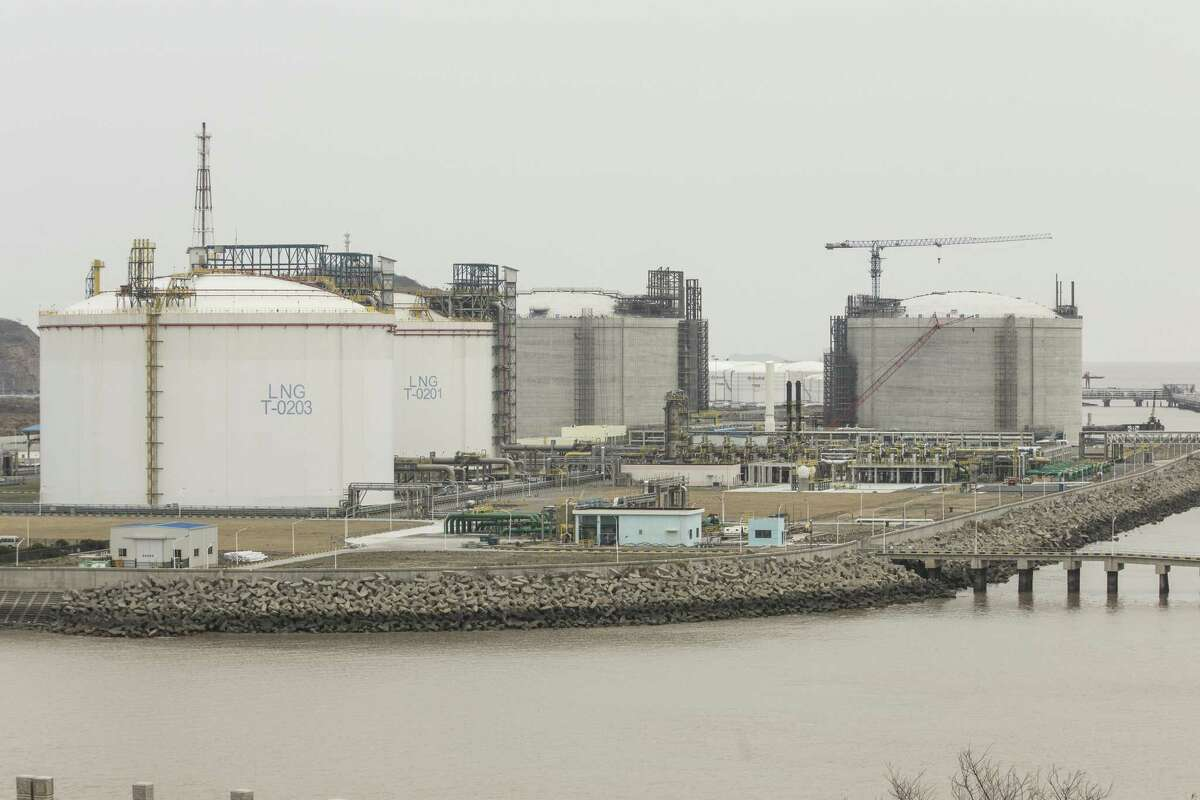 Under construction silos, right, stand next to storage silos at the liquid natural gas (LNG) terminal at the Yangshan Deep Water Port in Shanghai, China. Chinese officials are hoping the U.S. will agree to some flexibility on pledges in their phase-one trade deal.