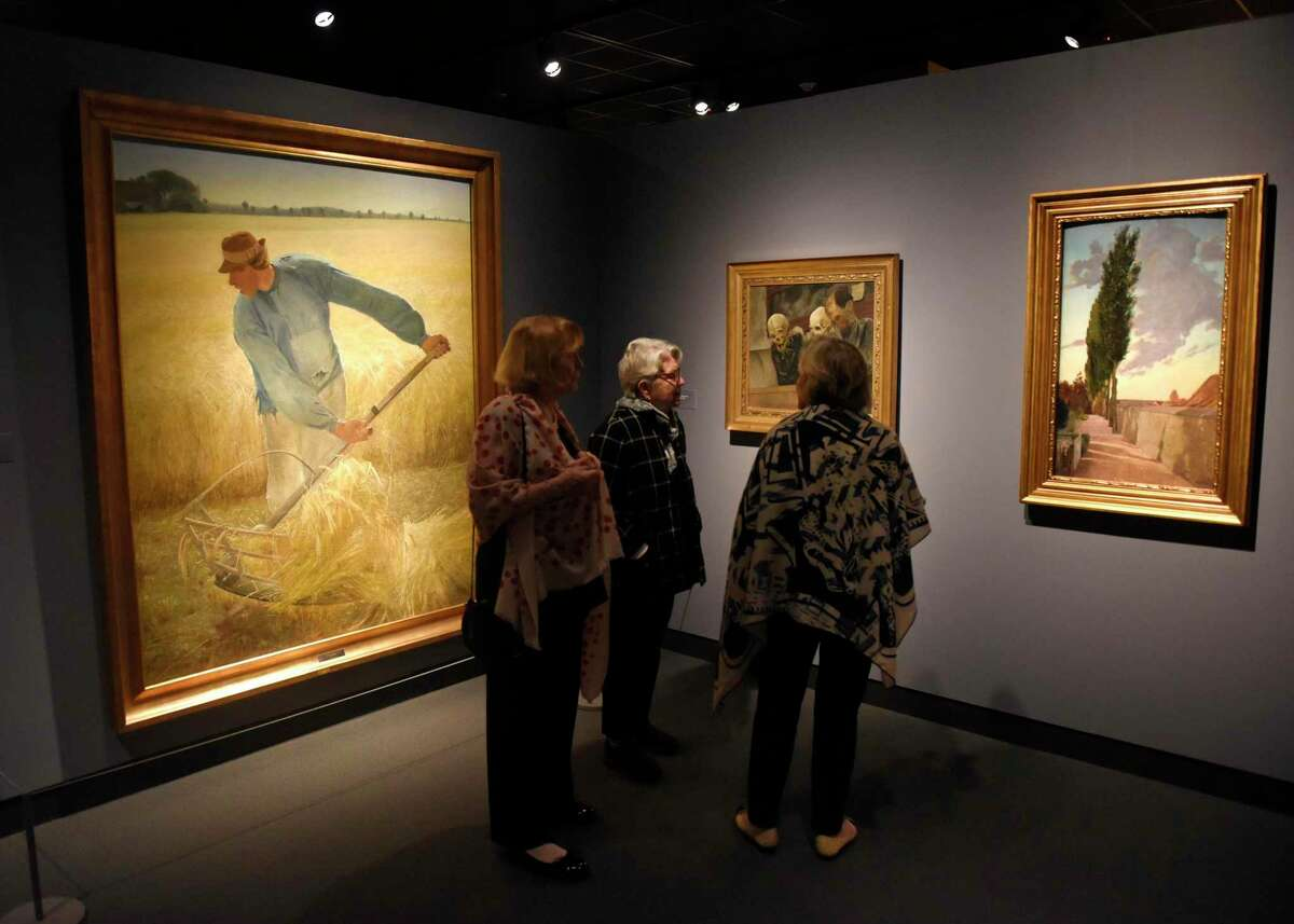 """Guests look at L.A. Ring's 1885 painting """"Harvest,"""" left, and others on display at the new """"On the Edge of the World: Masterworks by Laurits Andersen Ring from SMK-the National Gallery of Denmark"""" exhibition at the Bruce Museum in Greenwich, Conn. Sunday, Feb. 2, 2020."""