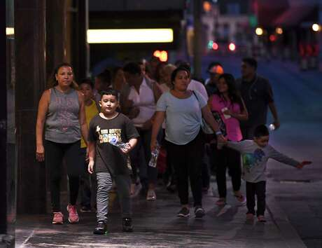 Central American migrants walk from the city's Migrant Resource Center to Travis Park Methodist Church, where they will sleep overnight on Wednesday, Aug. 14, 2019.