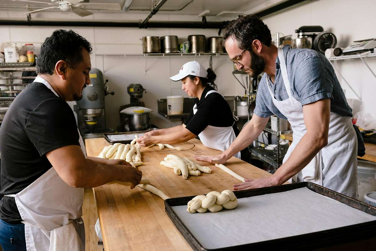 From left, Epifanio Garcia, Patty Rivas, and owner Sam Tobis roll dough for Challah bread at the Grand Bakery in Oakland, California, U.S. on Monday, Feb. 10, 2020.