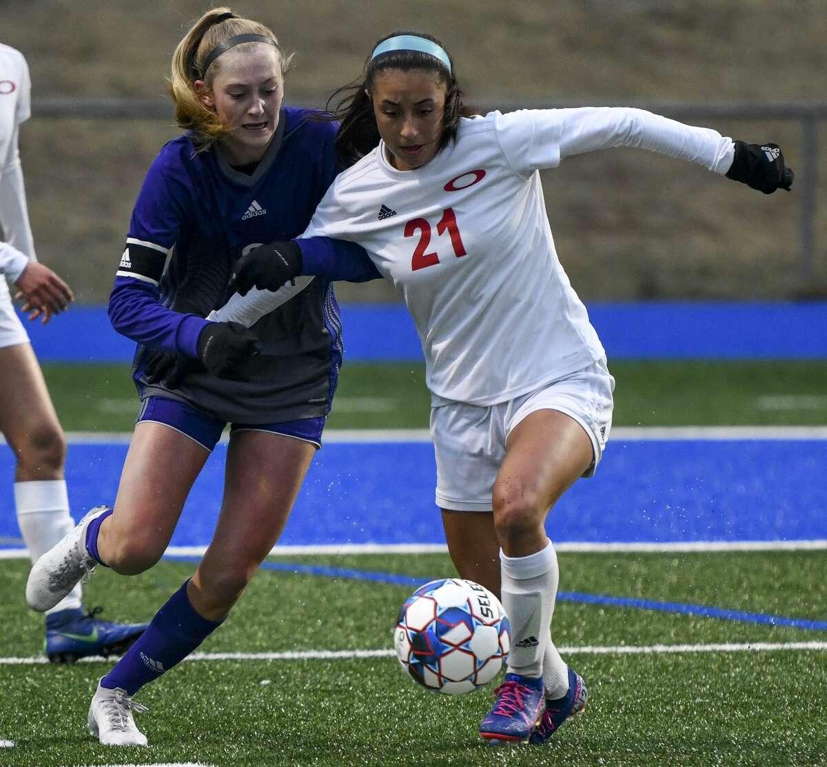 Midland High's Hannah Ware battles Odessa High's Yareli Barrera (21) for the ball on Tuesday, Feb. 11, 2020 at Grande Communications Stadium.