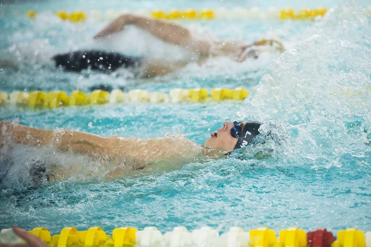 Midland's Lawrence Millward competes in the 100 yard backstroke during a meet against Dow Tuesday, Feb. 11, 2020 at H. H. Dow High School. (Katy Kildee/kkildee@mdn.net)