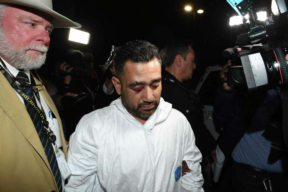 Michael Morales, suspect in two slayings, is walked out of the Bexar County Sheriffs Office on Tuesday night. He allegedly used a screw driver to kill a man over a drug debt, and then shot a woman afterward.
