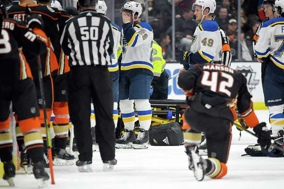 Blues defenseman Vince Dunn, left, of center wipes his faces as Anaheim Ducks defenseman Josh Manson kneels on the ice while Blues defenseman Jay Bouwmeester, who suffered a medical emergency, is worked on by medical personnel during the first period Tuesday night in Anaheim, Calif. Photo: AP Photo