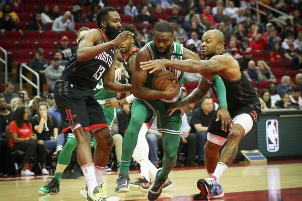 Houston Rockets guard James Harden (13) and Houston Rockets forward P.J. Tucker (17) attempt to stop Boston Celtics guard Jaylen Brown (7) from shooting the ball during the first half of an NBA basketball game at Toyota Center on Tuesday, Feb. 11, 2020, in Houston.