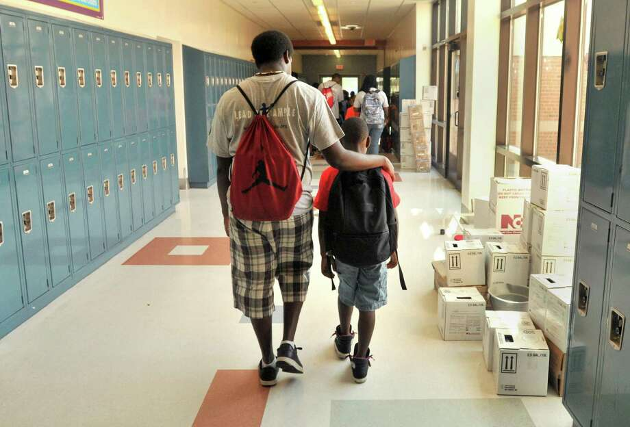 A LEAP summer programming counselor walks down a hallway with a student at Wexler-Grant Community School in New Haven. Photo: Hearst Connecticut Media File