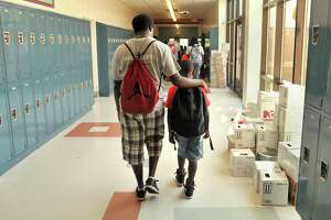 A LEAP summer programming counselor walks down a hallway with a student at Wexler-Grant Community School in New Haven.