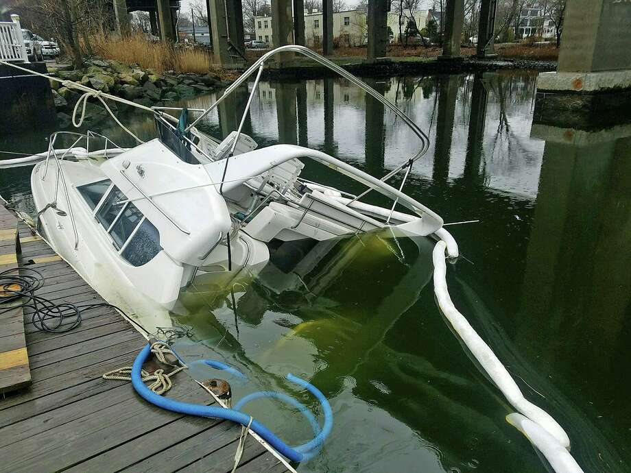 A partially sunken boat was found in the area of Riverscape Marina below an I-95 bridge on Tuesday, Feb. 11, 2020. Upon arrival, Marine Officers observed the vessel was leaking oil and requested Greenwich Fire Department respond with booms to contain the spill while employees of Harbors End attempted to de-water the vessel. Photo: Greenwich Police Photo