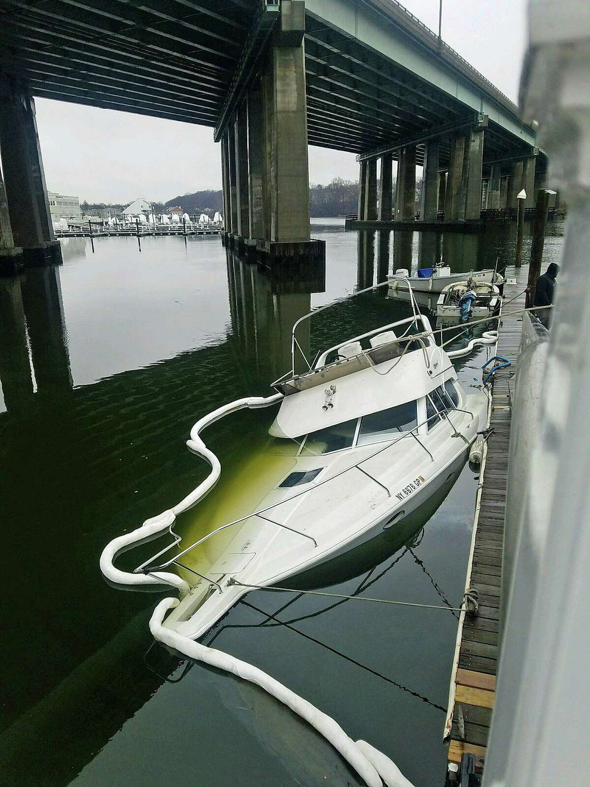 A partially sunken boat was found in the area of Riverscape Marina below an I-95 bridge on Tuesday, Feb. 11, 2020. Upon arrival, Marine Officers observed the vessel was leaking oil and requested Greenwich Fire Department respond with booms to contain the spill while employees of Harbors End attempted to de-water the vessel.