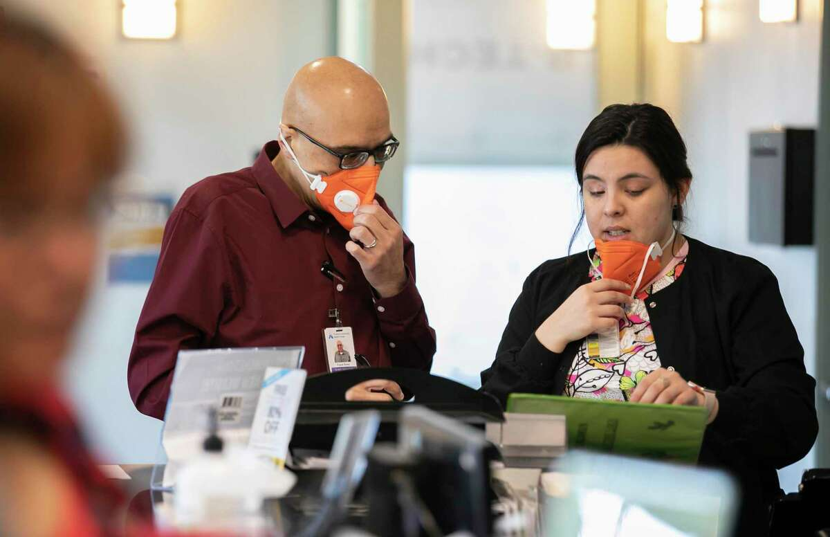 Wearing N95 face masks, from left to right, Clinic Manager Frank Perez and Back Medical Assistant Ericka Salcido confer at the front desk of the Foothill Community Health Center on Monday, February 10, 2020 in San Jose, California.