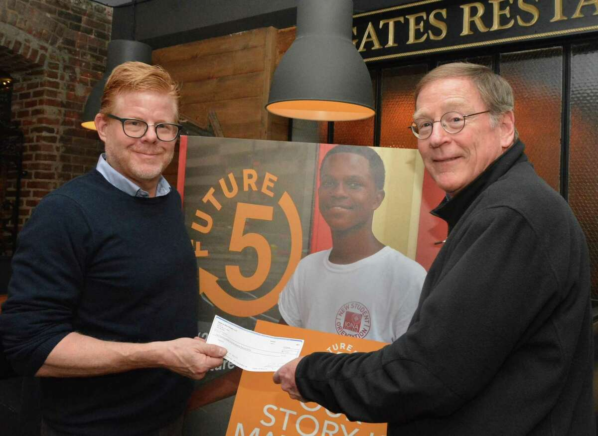 Gates Restaurant Owner Jay Luther presents a check to longtime New Canaan resident and Future 5 Founder Clif McFeely.