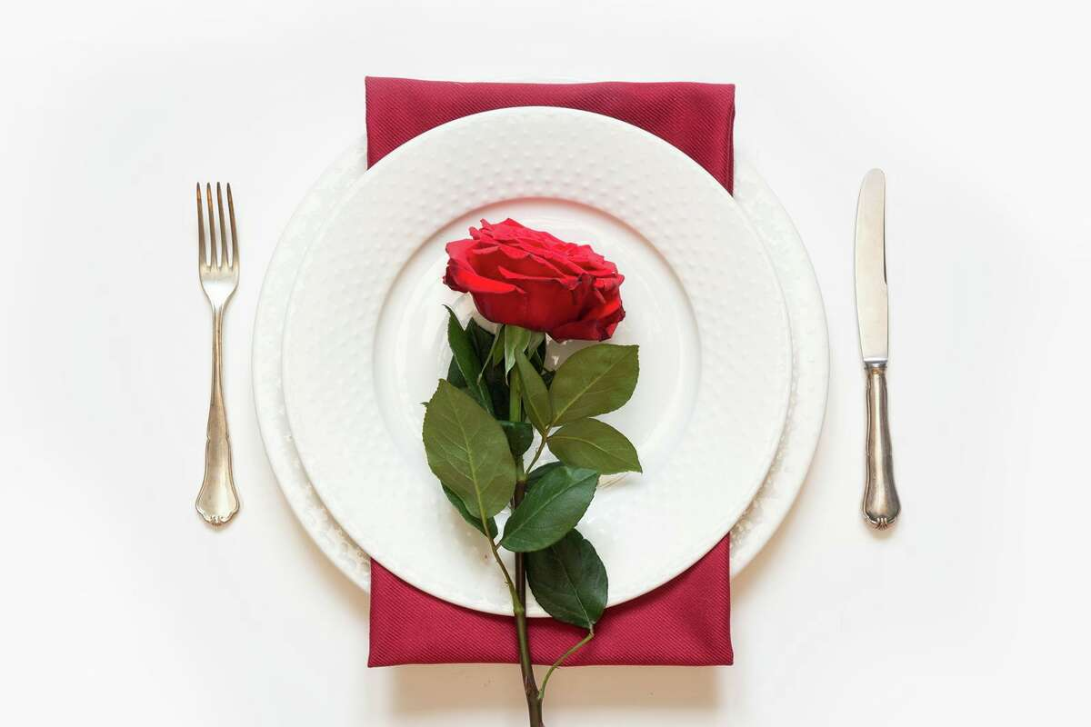 Valentine's day dinner with a romantic table setting with red rose.