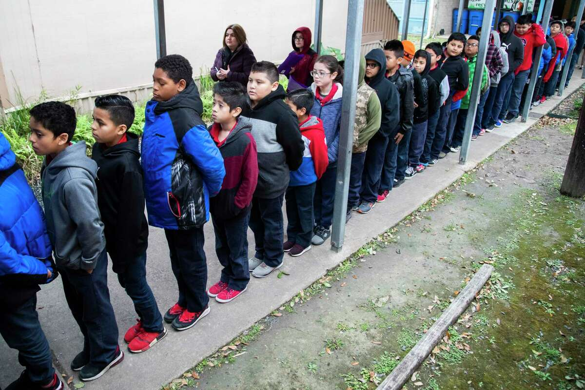Students at Houston ISD's Elrod Elementary School wait in line while wearing warm clothing on a late January morning. The school's outdoor hallways expose students to weather and create a safety concern, two reasons why district officials have suggested the 56-year-old campus could be rebuilt as part of a potential bond package.
