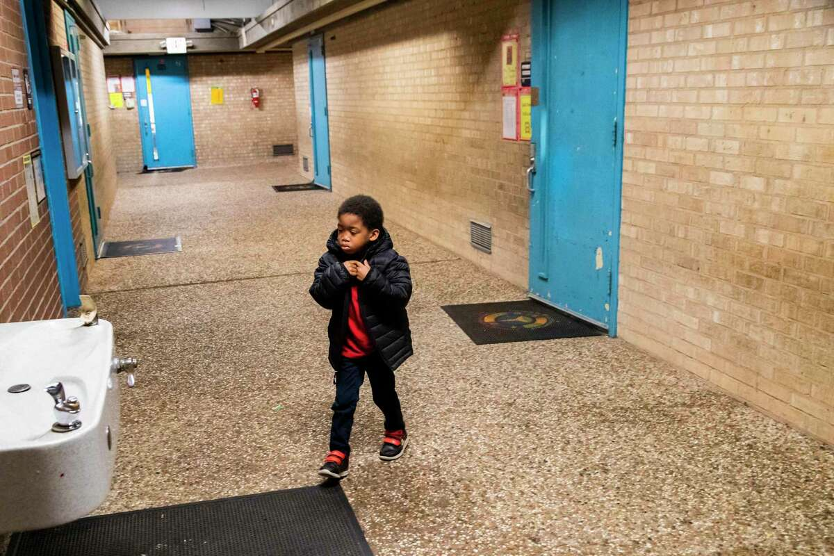 A preschool student wearing his winter coat at Houston ISD's Elrod Elementary School crosses the hallway from his classroom to have a sip of water from the fountain in late January. Elrod's hallways are not fully enclosed and protected from outdoor elements, a remnant of construction that took place in 1964.