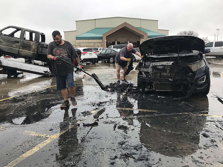 Joey Socia (left) and Jason Kotz with Airport Gulf Wrecker clean up as they tow vehicles damaged and destroyed in a car fire that broke out Wednesday morning in a Nederland High School parking lot. Photo taken Wednesday, February 12, 2020 Kim Brent/The Enterprise Photo: Kim Brent