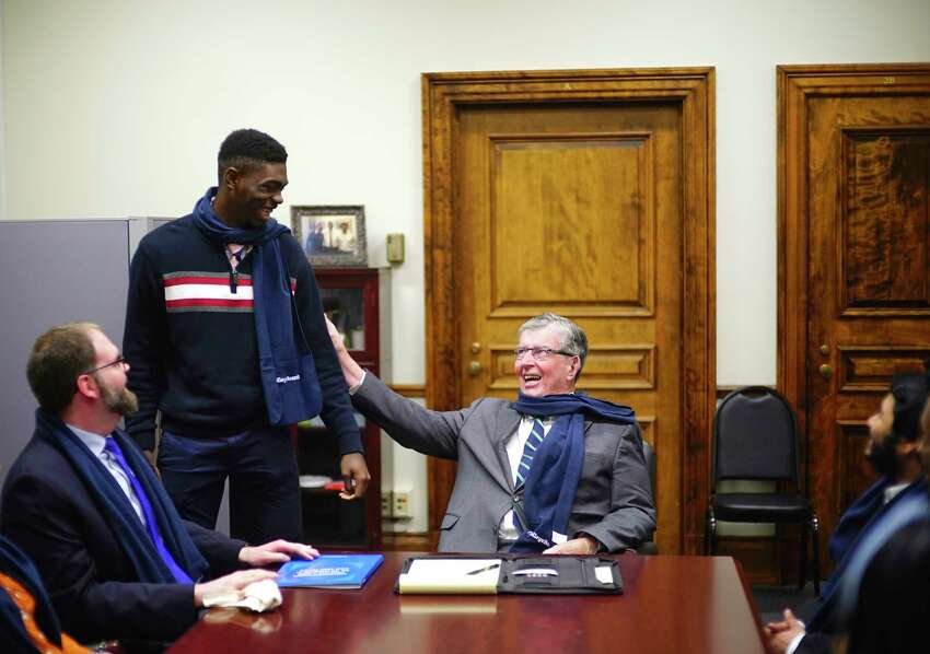 Albany High School senior Daniel Pollydore, left, and Senator Neil Breslin share a laugh after Pollydore wrapped a gifted scarf around the senator's neck during a visit by students in the school's AP Government class at the Capitol on Wednesday, Feb. 12, 2020, in Albany, N.Y. (Paul Buckowski/Times Union)