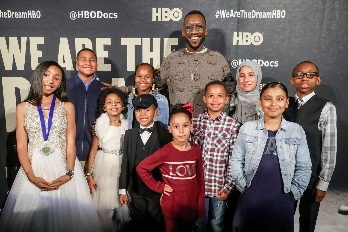 Executive producer Mahershala Ali (C) poses for a photo with young orators on the red carpet for