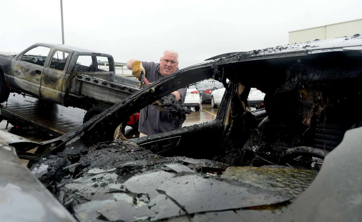 Jason Kotz, owner of Airport Gulf Wrecker, cleans up and loads vehicles for tow that were damaged or destroyed in a car fire that broke out in a parking lot at Nederland high School Wednesday morning. Photo taken Wednesday, February 12, 2020 Kim Brent/The Enterprise