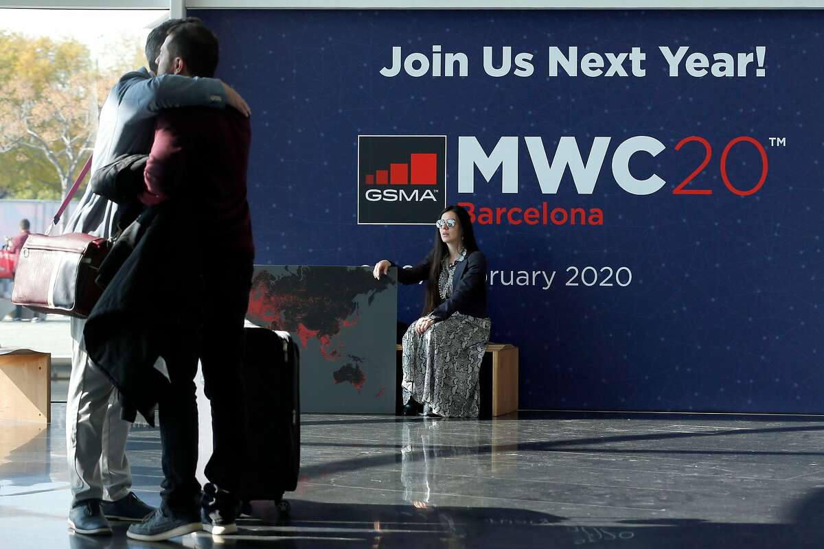 (FILES) In this file photo taken on February 28, 2019 a woman looks at two visitors hugging each other on the last day of the Mobile World Congress (MWC) in Barcelona on February 28, 2019. - Organisers of Spain�s World Mobile Congress 2020 cancelled the world's top mobile fair on February 12, 2020 after a string of industry heavyweights withdrew over the novel coronavirus, COVID-19, fears. (Photo by Pau Barrena / AFP) (Photo by PAU BARRENA/AFP via Getty Images)
