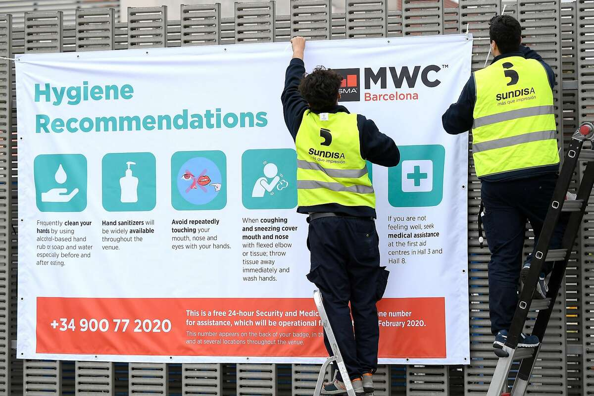 Workers install a banner with hygiene recommendations outside the Mobile World Congress MWC venue on February 12, 2020 at the Fira Barcelona Montjuic centre in Barcelona. - Organisers of the World Mobile Congress were holding urgent talks today over the fate of the world's top mobile fair after a string of industry heavyweights withdrew over coronavirus fears, a source close to the meeting said. (Photo by LLUIS GENE / AFP) (Photo by LLUIS GENE/AFP via Getty Images)