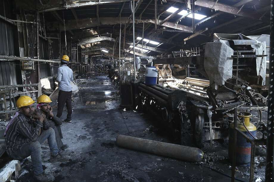 Laborers sit inside Nandan Denim, one of the largest denim suppliers in the world, after a fire swept the factory in Ahmedabad, India. At least seven people died in the blaze. Photo: Associated Press