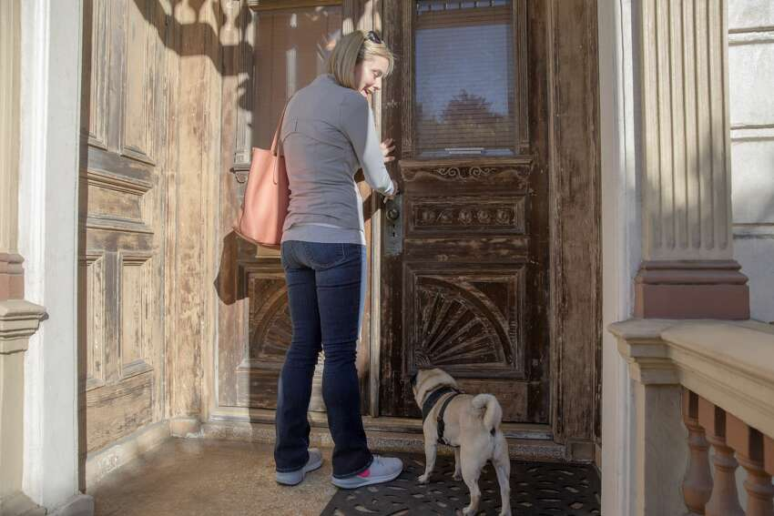 Leah Culver enters the front door of her recently purchased Painted Lady house on Steiner Street near Alamo Square in San Francisco with her dog Mr. Wiggles. The interior needs major renovations, and she is sharing her project to fix up the iconic Victorian home on her Instagram @pinkpaintedlady.