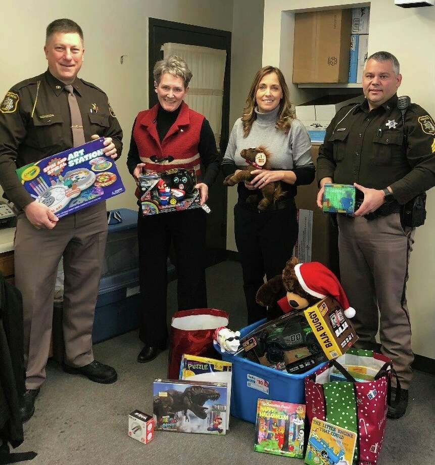 Personnel with the Mecosta County Sheriff's Office donated books, toys and puzzles from Bentley Thatcher's family to the Open Arms Child Advocacy Center on Tuesday. (Courtesy photo)
