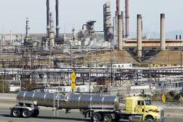 This March 9, 2010 file photo shows a tanker truck driving by the Chevron oil refinery in Richmond, Calif. The Obama administration is moving forward with a dramatic reduction in sulfur in gasoline and tighter emissions standards for cars, arguing the move will eventually save thousands of lives per year. The oil and gas industry warns the Environmental Protection Agency rules are unnecessary and will drive up gas prices. The rules will also add to the cost of buying a car. (AP Photo/Paul Sakuma, File)