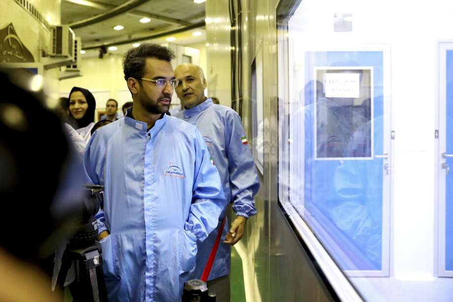 In this photo provided Saturday, Aug. 31, 2019, by Iran's Information and Communications Technology, Minister of Information and Communications Technology Mohammad Javad Azari Jahromi looks at The Nahid-1 domestically-built satellite at the space research center in Tehran, Iran. (Information and Communications Technology via AP) Photo: Information And Communications Technology Via AP