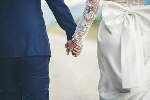 Couple holding hands before wedding.
