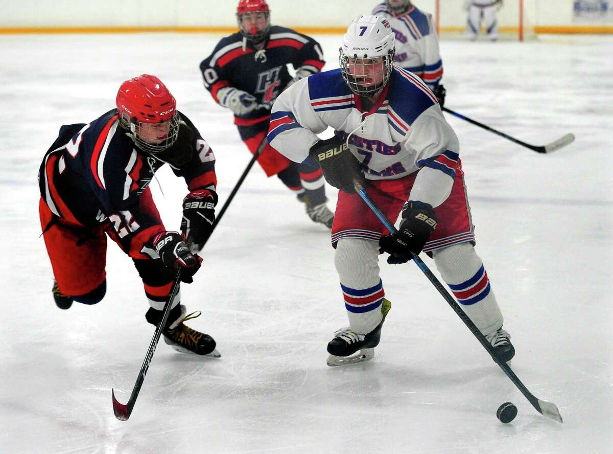 West Haven/Sacred Heart's Jenna Hunt (7) moves the puck as Hall/Conard's Greer Baumgartner converges during girls high school ice hockey action in West Haven, Conn., on Saturday Jan. 4, 2020.