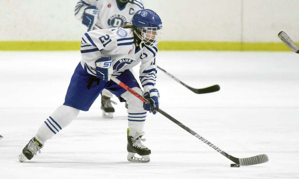 Darien's Kit Arrix (21) brings the puck through center ice during a girls ice hockey game against Simsbury at the Darien Ice House in January.