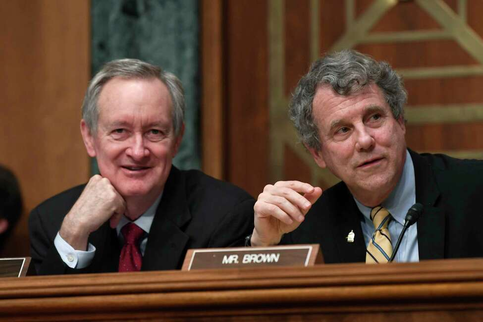 Senate Banking Committee Chairman Sen. Mike Crapo, R-Idaho, left, and ranking member Sen. Sherrod Brown, D-Ohio, right, talk during a hearing with Federal Reserve Chairman Jerome Powell on Capitol Hill in Washington, Wednesday, Feb. 12, 2020. (AP Photo/Susan Walsh)