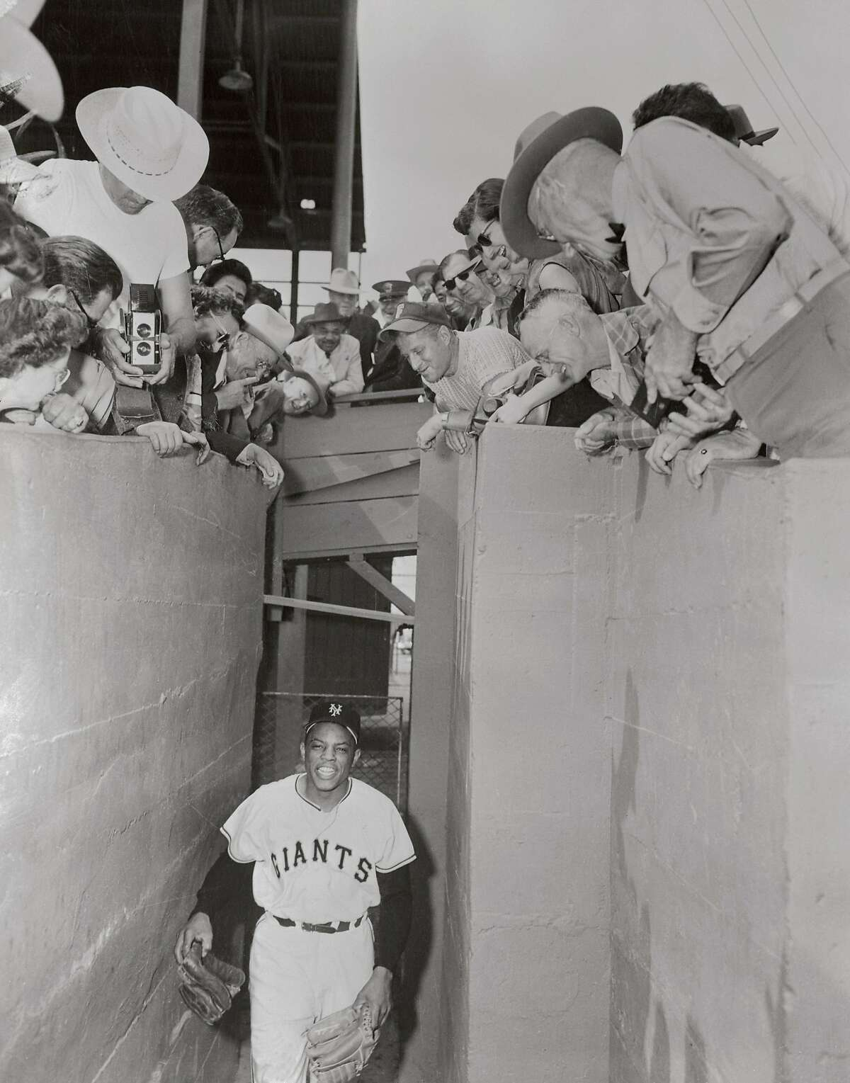 (Original Caption) Fans at New York Giants spring training camp watch Willie Mays as he comes from the locker room in this photo.