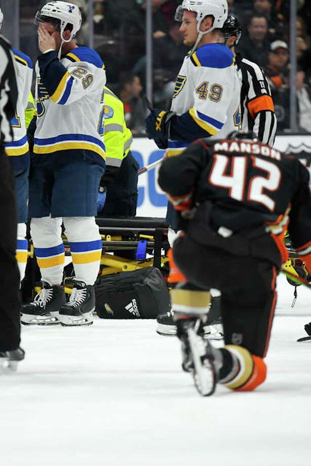 Blues defenseman Vince Dunn, left, wipes his faces as Anaheim Ducks defenseman Josh Manson kneels on the ice as Blues defenseman Jay Bouwmeester, who suffered a medical emergency, is worked on by medical personnel Tuesday night in Anaheim, Calif.