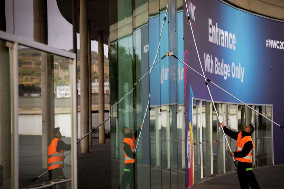 Workers clean the windows in one of the entrances at the Mobile World Congress 2020 venue in Barcelona, Spain, Tuesday, Feb. 11, 2020. Organizers of the worlda€™s biggest mobile technology fair are pulling the plug over worries about the viral outbreak from China. The annual Mobile World Congress show will no longer be held as planned in Barcelona, Spain, on Feb. 24-27. (AP Photo/Emilio Morenatti)