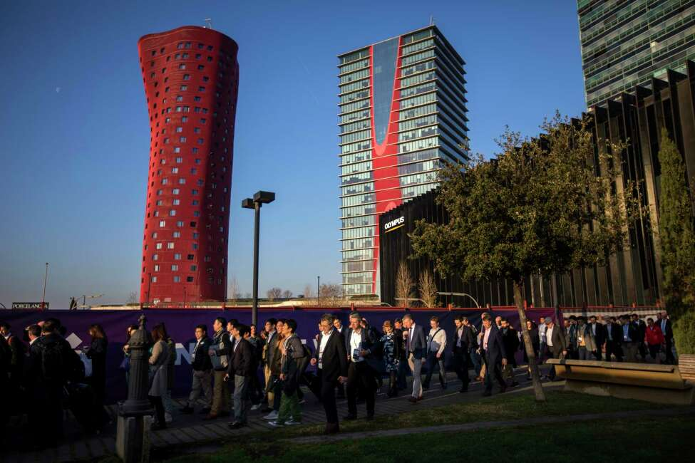 In this Feb. 25, 2019 photo, attendees walk to enter at the Mobile World Congress wireless show, in Barcelona, Spain. Organizers of the worlda€™s biggest mobile technology fair are pulling the plug over worries about the viral outbreak from China. The annual Mobile World Congress show will no longer be held as planned in Barcelona, Spain, on Feb. 24-27, 2020. (AP Photo/Emilio Morenatti)