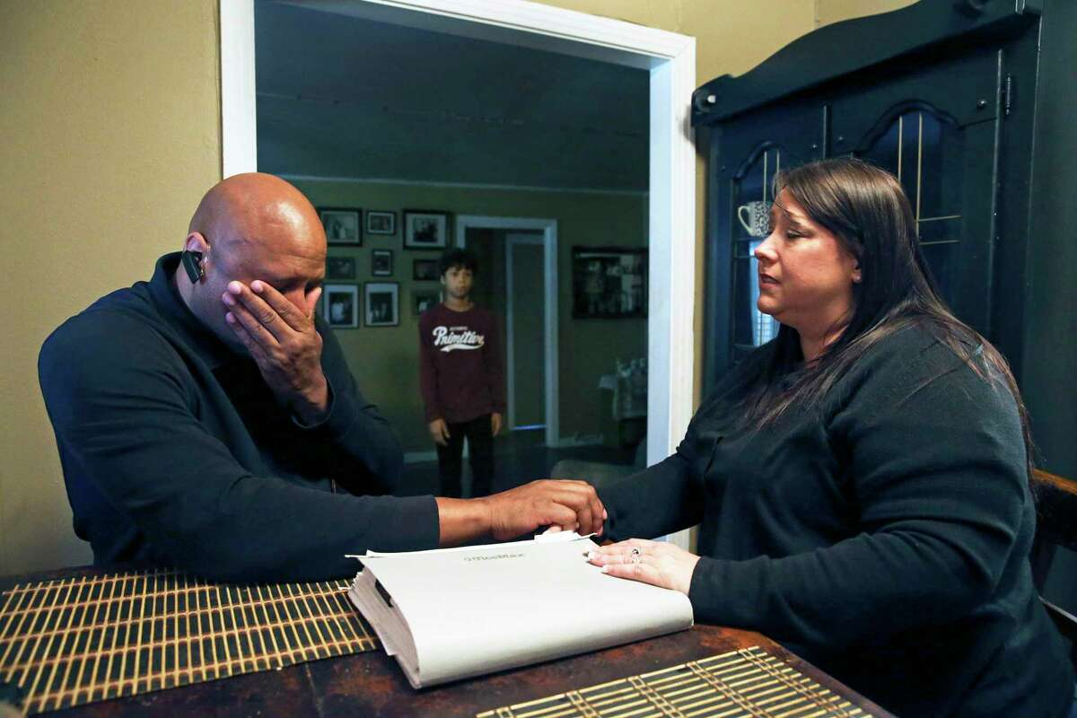 Hearing the distress of his parents, son Nathan, 14, approaches in the background as Ron and Ann Jones anguish in dealing with the massive headache of paperwork and worries on Feb. 6, 2020 after hiring Synergy, a company offering loan modification services.