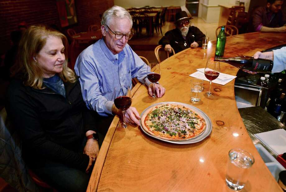 Westport residents and longtime patrons Rick and Ruth Edelson enjoy pizza and wine at the Fat Cat Pie Co. on Wednesday. Photo: Erik Trautmann / Hearst Connecticut Media / Norwalk Hour