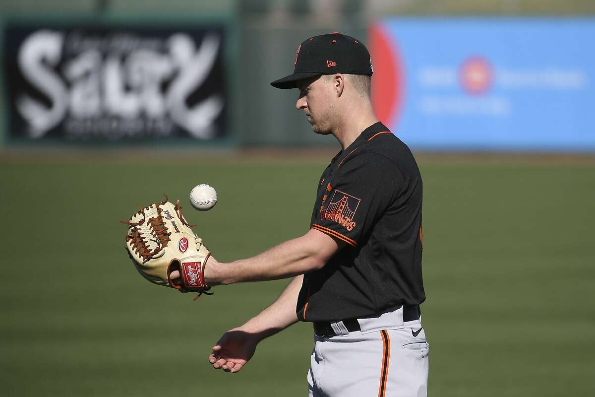 San Francisco Giants pitcher Trevor Gott flips the ball in the air during spring training baseball workouts for pitchers and catchers Wednesday, Feb. 12, 2020, in Scottsdale, Ariz. (AP Photo/Ross D. Franklin)
