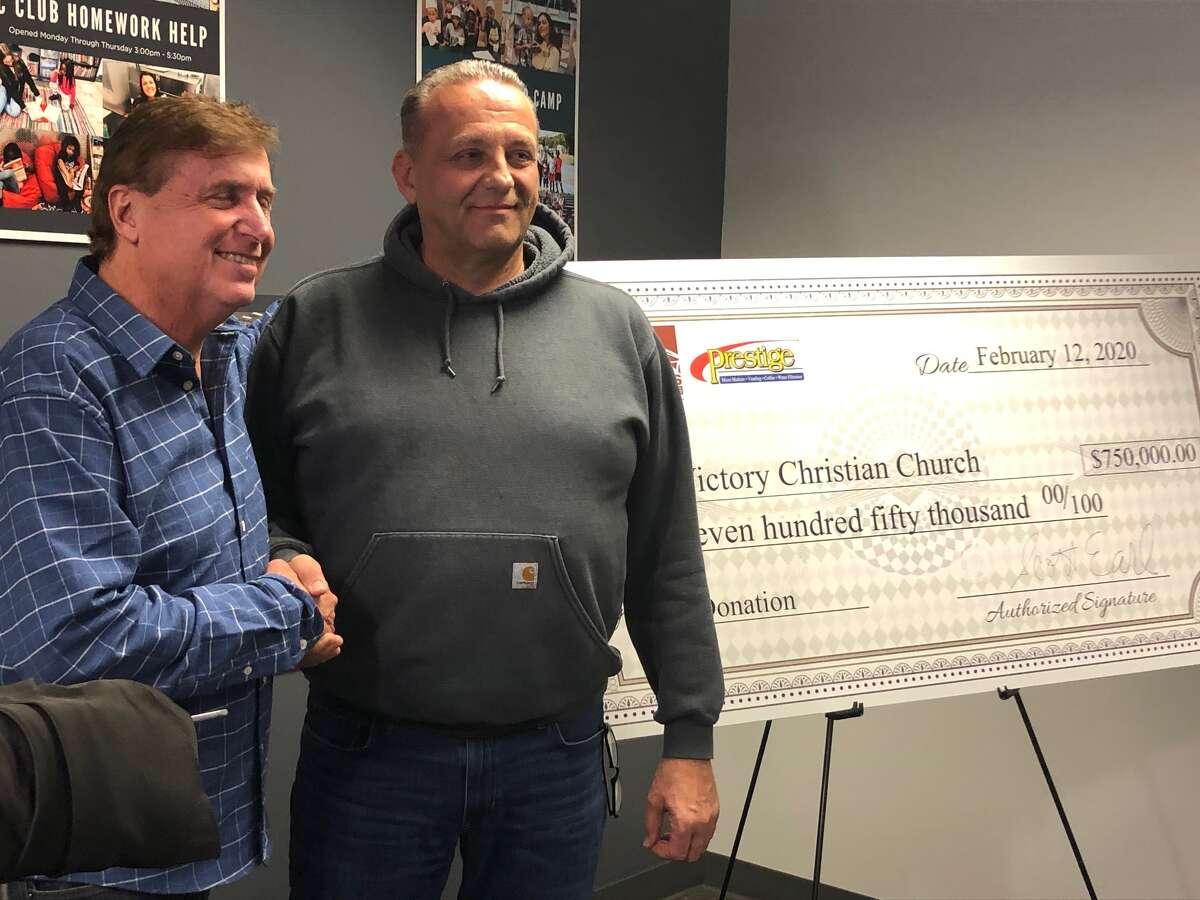 Scott Earl and Pastor Charlie Muller celebrate the donation Wednesday Feb. 12, 2020.