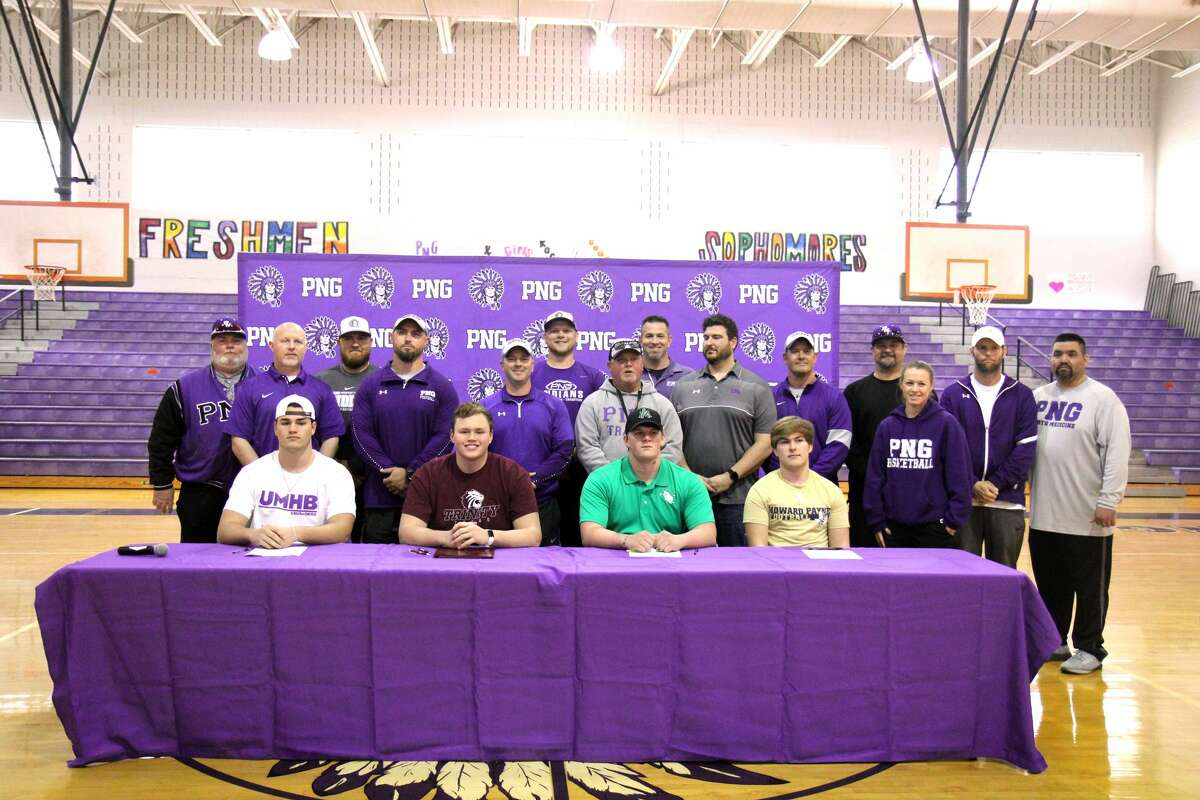 Port Neches-Groves football players, from left, Joshua Patteson, Trey Lisauckis, Jarrett Caillier and Caison Denzlinger sit in front of their coaches before the start of Wednesday afternoon's college signing ceremony in Port Neches.