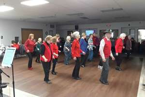 The Sullivan Senior Center members line dance during its 2019 Valentine's Day party. The center has been closed for activities because of the pandemic, but Director Joel Sekorski said he and his staff are keeping in touch with members with well-being checks, and outdoor lunches to keep people connected.