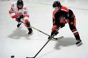 Ridgefield's Brendan Tierney (6) looks to intercept the puck as Fairfield Prep's Henry Keller (23) blocks during boys high school ice hockey action in Bridgeport, Conn., on Wednesday Feb. 12, 2020.