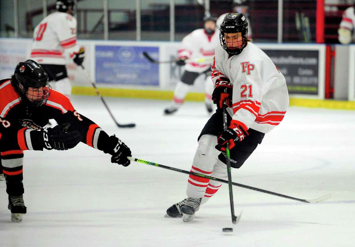 Ridgefield's Cornelius van Wees (8) reaches in to disrupt Fairfield Prep's Roberts Viguls (21) as he moves the puck during boys high school ice hockey action in Bridgeport, Conn., on Wednesday Feb. 12, 2020.