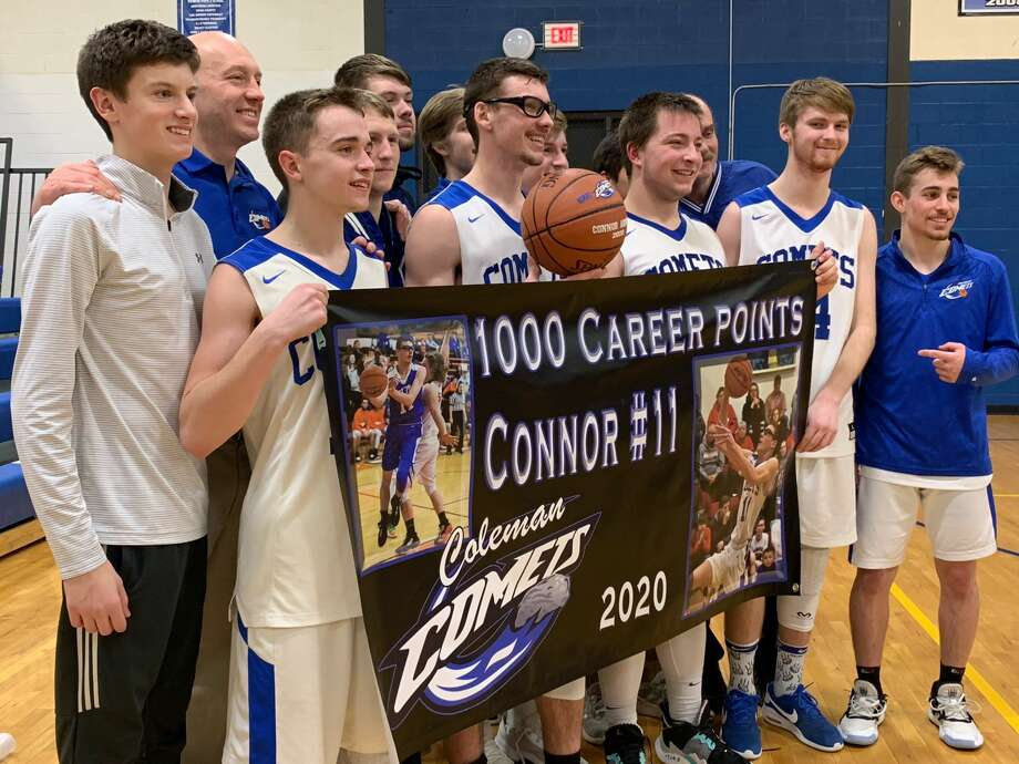 Coleman's Connor Arnold (holding ball) and his teammates celebrate a 63-56 win over Montabella and Arnold's historic 1,000th career point on Wednesday at the Comets' gym. Photo: Fred Kelly/fred.kelly@mdn.net