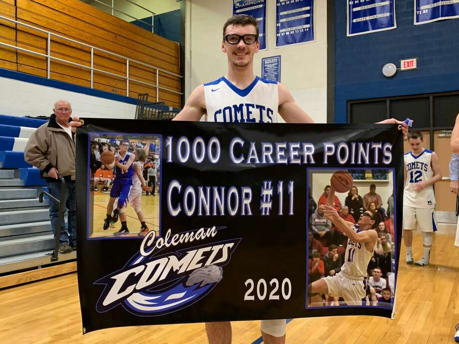 Coleman's Connor Arnold holds a banner commemorating his 1,000th career point on Wednesday at the Comets' gym. Photo: Fred Kelly/fred.kelly@mdn.net