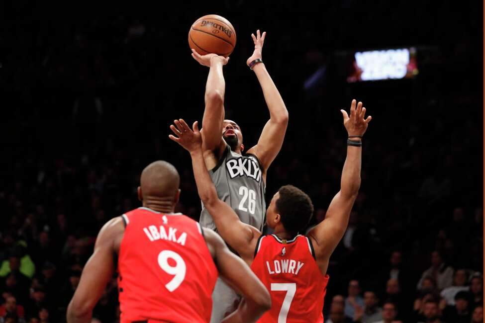 Brooklyn Nets guard Spencer Dinwiddie (26) shoots over Toronto Raptors center Serge Ibaka (9) and Toronto Raptors guard Kyle Lowry (7) during the second half of an NBA basketball game, Wednesday, Feb. 12, 2020, in New York. The Nets won 101-91. (AP Photo/Kathy Willens)