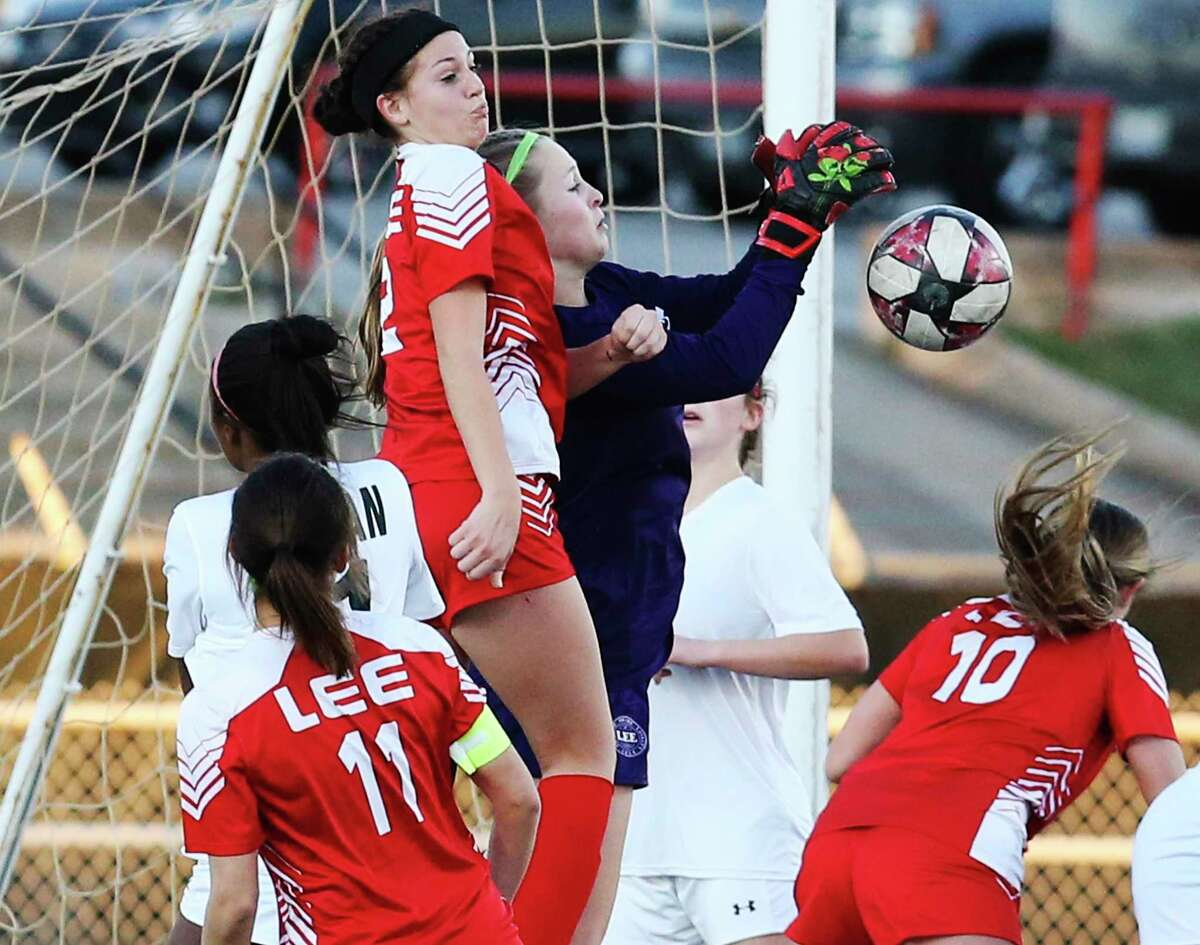 LEE goalkeeper Kaitlyn Zamagi deflects a shot with teammate Kameron Kloza (02) against Reagan during their girls soccer game at Commander Stadium on Wednesday, Feb. 12, 2020. LEE defeated Reagan, 1-0.