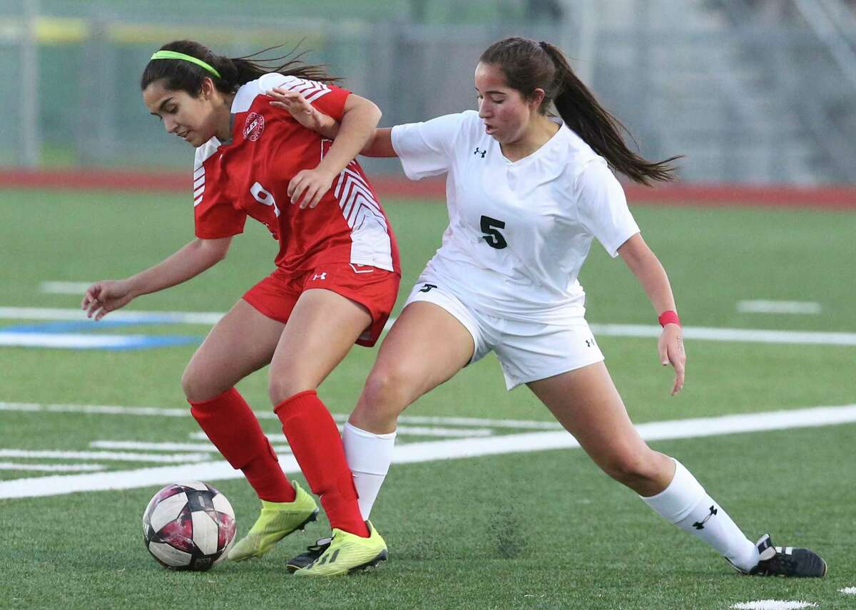 LEE's Victoria Castanon (09) battles with Reagan's Alexa Vela (05) for the ball during their girls soccer game at Commander Stadium on Wednesday, Feb. 12, 2020. LEE defeated Reagan, 1-0.
